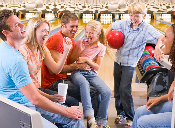 family laughing at bowling alley